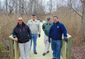 "Paved Millstream Trail and reconstructed bridges open to all. Left to right: Former Council Member Frank Ogens, Council Member Jim Beauchamp, Council Member George ""Smokey"" Sigler and Council Member Tim McCluskey."